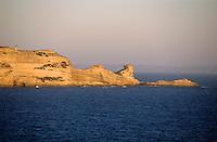 Calcareous cliffs seen across the blue Mediterranean Sea at sunset, Bonifacio, Corsica, France.