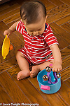 9 month old baby finding toy bells hidden in plastic pot with lid
