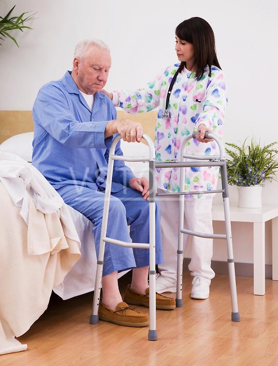 Nurse helping senior man walk with frame
