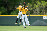 FCL Pirates Gold outfielders Jasiah Dixon (6), Randy Romero (23), and Daniel Rivero (27) celebrate after the final out of a game against the FCL Red Sox on July 1, 2021 at Pirate City in Bradenton, Florida.  (Mike Janes/Four Seam Images)