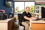 September 18, 2014. Raleigh, North Carolina.<br />  Chuck Sawyer poses for a portrait at his desk at the main retail and production franchise.<br />  Chuck Sawyer, 37, is the owner of three Instant Imprints franchises, specializing in promotional materials such as t-shirts,signs and mugs. Sawyer wishes he had more saved for retirement and is encouraging his none employees to start thinking about how they will save for when they get older.<br /> Publication: AARP Bulletin<br /> Editor: Jenna Isaacson-Fuller<br /> Model Released<br /> Portrait