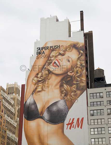 Hand Painted Fashion Advertising Billboard on the Side of a Building in Midtown Manhattan, 8th Avenue and 34th Street, New York, New York USA.<br /> <br /> AVAILABLE FROM JEFF FOR EDITORIAL LICENSING ONLY (INSIDE A MAGAZINE OR OTHER EDITORIAL PUBLICATION).<br /> <br /> NOT AVAILABLE FOR ANY SORT OF COMMERCIAL OR ADVERTISING LICENSING BECAUSE THE BILLBOARD IS NOT MODEL OR PROPERTY RELEASED.<br /> <br /> AVAILABLE FROM JEFF AS A FINE ART PRINT.<br /> <br /> This is one of the few remaining locations in New York City (due to the unusual shape of the building) where advertising billboards are still created the old fashioned way.....hand painted by billboard artists suspended on scaffolding high above the city streets!