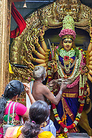 Hindu Temple Sri Vadapathira Kaliammam during Navarathiri Celebrations, Singapore.  Hindu Priest Performing Ritual before Hindu Deity.