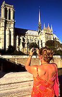 Woman tourist taking picture of the Notre Dame Cathedral in Paris France