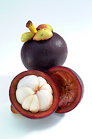 Studio photo of whole and sectioned mangosteen on white background.