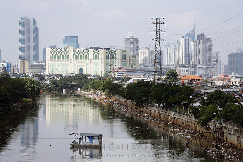 A small passenger bat crosses a canal in the main urban area of Jakarta. The canals were originally built to help the city cope with flooding however they have fallen into disrepair and are now clogged with refuse and human waste that is discarded into the waterway.