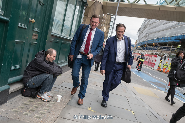 Workers in the London Bridge business district walk past a homeless man.