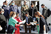 Pictured: A man has his hands sanitised by health workers as he disembarks to Ierapetra Thursday 27 November 2014<br />