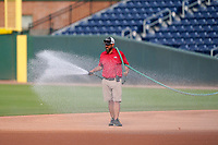 Head groundskeeper Greg Burgess of the Greenville Drive sprays the infield before a game against the Asheville Tourists on Tuesday, June 1, 2021, at Fluor Field at the West End in Greenville, South Carolina. (Tom Priddy/Four Seam Images)