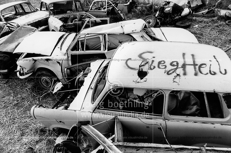 GERMANY in 1990, former East Germany, German Democratic Republic GDR, typical plastic car Trabant with fascist Nazi Hitler greeting Sieg Heil on wild dumping site in village Plauerhagen, Mecklenburg, black and white image with film grain