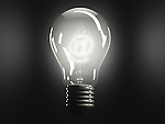Illustrative image of lit bulb with at symbol representing business idea