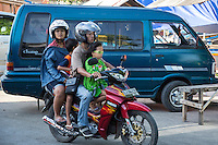 Jimbaran, Bali, Indonesia.  Family on Motorbike.  Adults with Helmets, Children Without.