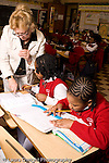 K-8 Parochial School Bronx New York Grade 3 mathematics lesson on measurement using rulers female teacher looking over student's work vertical