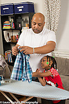 household chores 5 year old girl observing and learning how to iron helped by her father