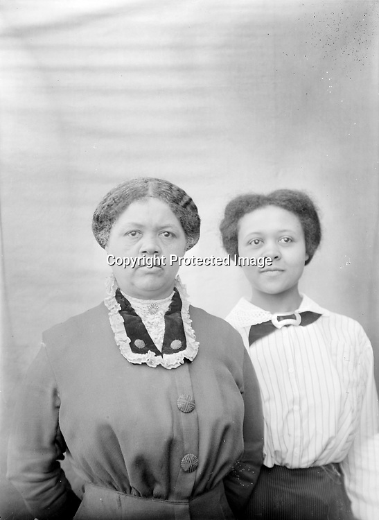 FRANCES HILL AND MATRON. Frances Hill (1904-1932) stands demurely behind an older woman--perhaps her mother? Hill boarded with John C. Galbreath's family even before she graduated from Lincoln High School in 1924 and as late as 1929. Galbreath also provided her grave at Wyuka Cemetery upon her young death in 1932. (Frances Hill appears in other images)<br /> <br /> The 1920 census shows Aaron Douglas, 21 year old University student, was a roomer in the household of Ben. F. & Lottie Corneal. Ben was head of the waiters club of Lincoln; a second roomer was a barber. They resided at 524 N. 9th--a couple of blocks south of Mamie Griffin's house at 915 U. The Corneals next door neighbors were John and Mable Galbreath at 524 N. 9th. John was sometimes a waiter; in 1920 he was listed as operating a restaurant. John and Mable also had a roomer, as well as a stepdaughter--15 year old Frances Hill. <br /> <br /> Photographs taken on black and white glass negatives by African American photographer(s) John Johnson and Earl McWilliams from 1910 to 1925 in Lincoln, Nebraska. Douglas Keister has 280 5x7 glass negatives taken by these photographers. Larger scans available on request.