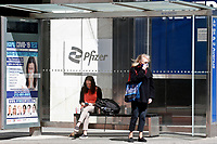NEW YORK - NEW YORK - MARCH 23:  Women wait for a bus in front of Pfizer World Headquarters on March 23, 2021 in New York. The Food and Drug Administration (FDA) says Pfizer's coronavirus vaccine can be stored in normal freezers for two weeks, instead of storage at ultra-cold temperatures. (Photo by John Smith/VIEWpress)