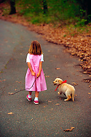 Five year old girl walking with her golden retriever puppy.