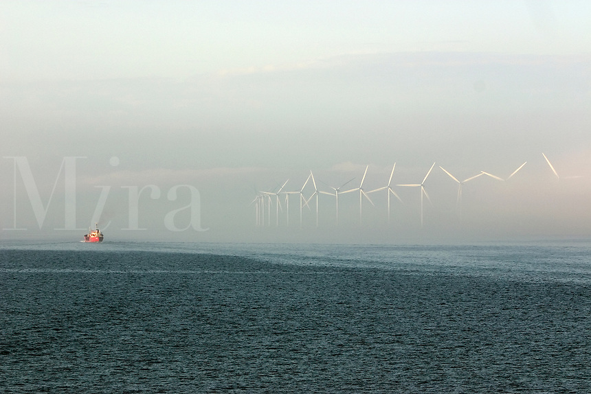 Cargo ship passing giant wind turbines as it leaves Copenhagen, Denmark harbour