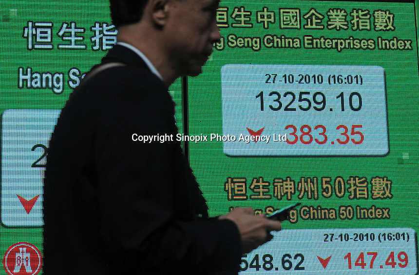 A passerby walks by a large-size electronic board which indicates the Hang Seng Index(HSI) and Heng Seng China Enterprises Index, Hong Kong SAR, China. The Hang Seng Index is a freefloat-adjusted market capitalization-weighted stock market index in Hong Kong. It is used to record and monitor daily changes of the largest companies of the Hong Kong stock market and is the main indicator of the overall market performance in Hong Kong..