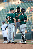 Greensboro Grasshoppers pitching coach Matt Ford (52) meets with starting pitcher Tahnaj Thomas (17) and catcher Dylan Shockley (29) during the game against the Winston-Salem Dash at Truist Stadium on June 17, 2021 in Winston-Salem, North Carolina. (Brian Westerholt/Four Seam Images)