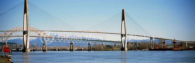 Bridges over Fraser River - New Westminster to Surrey, BC, British Columbia, Canada - Skytrain on SkyBridge, Patullo Bridge, and Train Bridge - Golden Ears (Coast Mountains) in background - Panoramic View