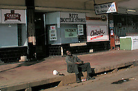 A man sits on the pavement outside a bottle store in Bulawayo.