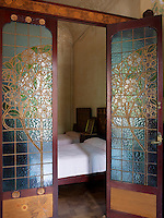 Twin beds on the first floor are concealed behind a wooden partition with stained glass doors to let in the light