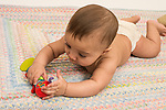 Infant boy age 6 months in diaper on stomach grasping and touching colorful cloth toy that makes sounds with touched