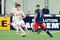 FOXBOROUGH, MA - MAY 22: Caden Clark #37 of New York Red Bulls comes in to tackle Gustavo Bou #7 of New England Revolution during a game between New York Red Bulls and New England Revolution at Gillette Stadium on May 22, 2021 in Foxborough, Massachusetts.