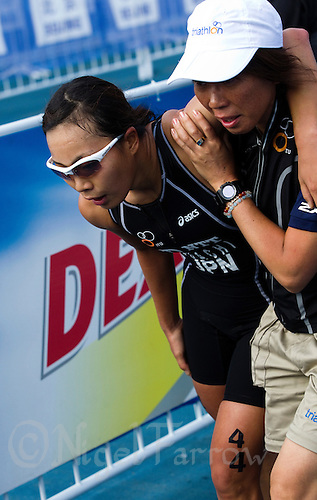11 SEP 2011 - BEIJING, CHN - Mariko Adachi (JPN) is helped from the finish line by an official after completing the 2011 Elite Womens ITU World Championship Series Grand Final Triathlon .(PHOTO (C) NIGEL FARROW)