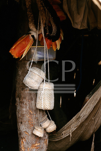 Assurini Indians, Amazon, Brazil.  Artifacts hanging from a pole.