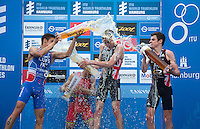 12 JUL 2014 - HAMBURG, GER - Alistair Brownlee (GBR) (second from the right) from Great Britain  celebrates  winning the elite men's 2014 ITU World Triathlon Series round in the Altstadt Quarter, Hamburg, Germany, with silver medalist Vincent Luis (FRA) (left)  from France and bronze medalist Jonathan Brownlee (GBR) (right) also from Great Britain as series leader Javier Gomez (ESP) (second from the left) from Spain steps off the podium (PHOTO COPYRIGHT © 2014 NIGEL FARROW, ALL RIGHTS RESERVED)