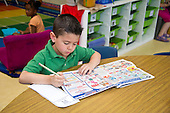 MR / Schenectady, NY. Zoller Elementary School. Kindergarten. Student (boy, 5) writes a shopping list by choosing words from newspaper advertisements as a literacy activity during learning center time. MR: Oco5. ID: AL-gKs. © Ellen B. Senisi