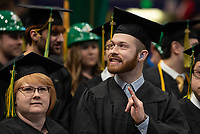 """Dalton Arnes, Certificate Diesel Power Technology, A.A.S. Diesel Power Technology, signs """"I love you"""" to family in the audience as he waits to receive his degree during UAA's 2019 Fall Commencement at the Alaska Airlines Center."""