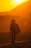 A male street vendor of sunglasses walks at sunset in Kino Bay, Sonora, Mexico. backpack on the back<br /> (Photo: Luis Gutierrez / NortePhoto.com).<br /> <br /> Un hombre vendedor ambulante de lentes para el sol camina al ataredecer en la bahia Kino, Sonora, Mexico. mochila en la espalda<br /> (Photo: Luis Gutierrez / NortePhoto.com).