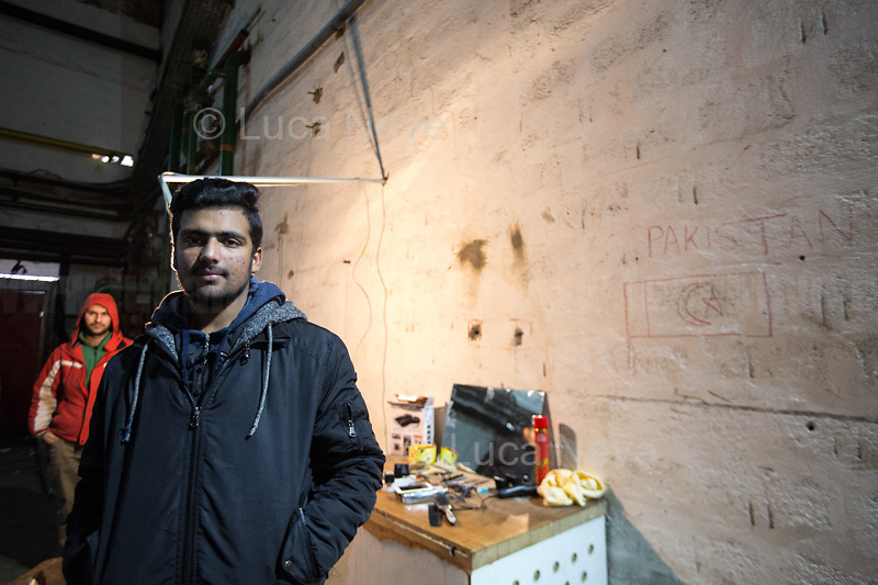 """Waqas Ali from Pakistan, at the hairdresser & barber shop. <br /> <br /> Bihać, Bosanska Krajina, Bosnia, 15/12/2018.The Bira camp is a former fridge factory located outside Bihac. It is managed by the UN (ONU) agency called IOM (OIM) - International Organization for Migration. The camp is a huge hangar and it composed by tents and containers (mainly located in the area dedicated to most vulnerable people and families) 'donated' by the EU, Turkkizilayi, Crveni Kriz Grada Bihaca. The camp has got also a Health clinic, the """"Klinika"""", provided by DRC Danish Refugee Council and UNHCR and EU (UE). The People met outside the Klinica who showed their medical refers, their wounds and injuries claimed that they were beaten up by the Croatian Police which also allegedly stole their money and broke their smartphones after they were found trying to cross the border between Bosnia & Croatia, the beginning of the so called """"The Game"""" (1.). The very dangerous end of the """"Balkan route"""", the undetected border crossing throughout Croatia and then Slovenia, which people try numerous times to reach Italy or Austria. If they caught crossing any of the borders, they will be deported back to Bosnia, at """"square 1 of the Game"""".<br /> Clothes, food and a little bit of entertainment for the Children are provided by the Crveni Kriz Grada Bihaca, the Bosnian Red Cross, which also manages a sort of canteen.<br /> The IOM (OIM) provided data about the People living in the Bira camp while this reportage was made:<br /> -2067 people are the inhabitant of the camp (but obviously the number changes a lot and often)<br /> -187 unaccompanied minors all boys, mostly from Pakistan;<br /> -80 families: 325 family members, 145 children, 78 boys, 67 Girls.<br /> Moreover, the IOM (OIM) informed journalists that 550 People will go to the Borici camp when it's restructured and refurbished, mainly the most vulnerable people: families and unaccompanied minors.<br /> <br /> 1. http://bit.do/fgwYL"""
