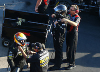 Aug 15, 2014; Brainerd, MN, USA; Crew members help NHRA funny car driver Jeff Arend (bottom) and Chad Head put on their helmet and safety equipment during qualifying for the Lucas Oil Nationals at Brainerd International Raceway. Mandatory Credit: Mark J. Rebilas-