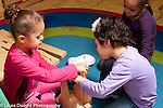 Education Preschool 3-4 year olds two girls building together with wooden blocks