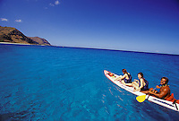 Kayaking off Oahu's Makua Beach in clear blue water, Japanese tourist girls and guide