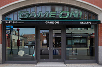 """Game On!, a bar and restaurant next to Fenway Park, is temporarily closed due to the ongoing Coronavirus (COVID-19) global pandemic, in Boston, Massachusetts, on Wed., Jan. 6, 2021. A sign on the door states that they will be closed until Spring 2021 and implores people to think about restaurant workers during these difficult times, """"But no matter where you do go, please tip your servers well. It's tough times out there for them,"""" the sign says."""