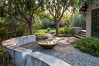Cement wall defining backyard garden room unwatered space with gravel patio and water bowl fountain; Moore Garden Los Altos, California; Ground Studio Landscape Architecture