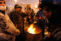Protesters around a bonfire fight the cold snap that invaded  Kiev while the city prepares for a predictably  violent attack from the police.  Tonight the  police is expected to forcedly evacuate the streets from the protesters blocking all the government buildings. Kiev. Ukraine.