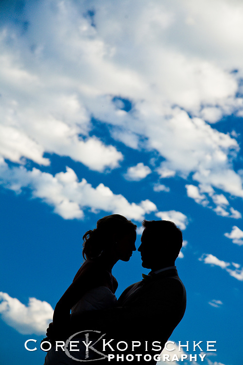 Bride and groom silhouetted with the clouds at a country wedding in Steamboat springs Colorado.