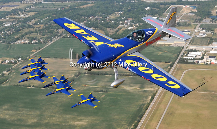 The United States Navy Blue Angels and world-renowned aerobatic pilot Michael Goulian form up for a flight over Dayton Municipal Airport in Vandalia, Ohio on July 5, 2012 as the 2012 Vectren Dayton Airshow prepares to get underway this weekend.