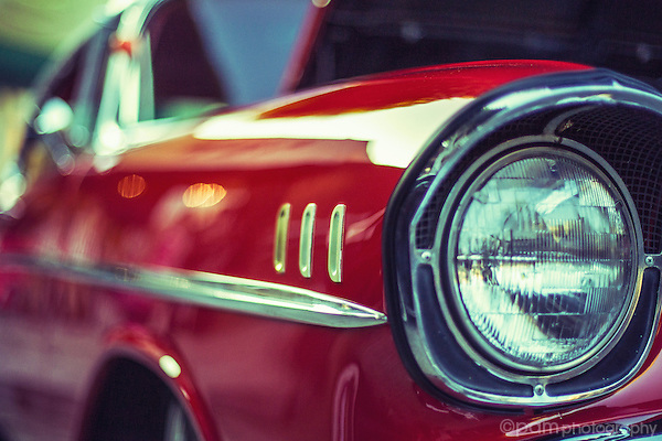 Classic red car with emphasis on the headlight.