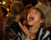 Children play in in a snowfall of fake snow during the annual Christmas tree lighting event at Birkdale Village in Huntersville, NC. Birkdale Village combines the best of shopping, dining, apartments and entertainment venues within a 52-acre mixed-use development.