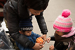 Preschoool toddler 2s out at market in fall, exploring small gourds and squash