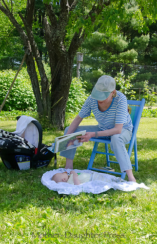 Little reader: Baby gets a chance to view the book, Community Garden, Maine, USA