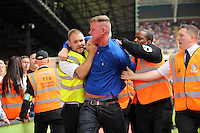 Pictured: A Swansea supporter is escorted off the ground by security stewards<br />