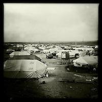 """Fluechtlingscamp fuer 4-5.000 Jeziden die vor der Terrororganisation Islamischer Staat (IS) aus dem Singal-Gebirge gerettet wurden.<br /> Das Camp unweit der Stadt Derik in der Provinz Cizire vom Kurdischen Roten Halbmond (Heyva Sor A Kurd), dem britischen """"International Rescue Center"""" und der Bevölkerung aus der Umgebung errichtet. Das Fluechtlingshilfswerk der Vereinten Nationen UNHCR brachte spaeter Zelte, Decken, Medikamente und Teppiche fuer die Fluechtlinge.<br /> Tuerkischen und Syrischen Kurden der PKK und YPG/YPJ gelang es im August 2014 ca. 125.000 Jeziden zu retten nachdem die irakischen Peschmerga ihre Landsleute im Stich gelassen hatten. Unterstuetzt wurde die Rettung durch 6.000 Menschen aus der Region um die Stadt Derik, die mit ihren Privatfahrzeugen in das Sindschar-Gebirge gefahren sind, um die Jeziden zu retten. Etliche der Retter wurden bei dieser Aktion vom IS ermordet und nicht alle Jeziden konnten gerettet werden. So blieben Kaempfer der YPG/YPJ und der PKK im Sindschar-Gebirge im Irak um die verbliebenen 10.000 Menschen vor dem IS zu schutzen.<br /> Die Irakischen Peschmerga trauten sich erst vier Monate spaeter im Dezember 2014 mit US-Unterstuetzung wieder in die Gegend um die letzten ihrer Landsleute zu retten.<br /> 18.12.2014, Derik/Rojava/Syrien<br /> Copyright: Christian-Ditsch.de<br /> [Inhaltsveraendernde Manipulation des Fotos nur nach ausdruecklicher Genehmigung des Fotografen. Vereinbarungen ueber Abtretung von Persoenlichkeitsrechten/Model Release der abgebildeten Person/Personen liegen nicht vor. NO MODEL RELEASE! Nur fuer Redaktionelle Zwecke. Don't publish without copyright Christian-Ditsch.de, Veroeffentlichung nur mit Fotografennennung, sowie gegen Honorar, MwSt. und Beleg. Konto: I N G - D i B a, IBAN DE58500105175400192269, BIC INGDDEFFXXX, Kontakt: post@christian-ditsch.de<br /> Bei der Bearbeitung der Dateiinformationen darf die Urheberkennzeichnung in den EXIF- und  IPTC-Daten nicht entfernt werden, diese sind in digital"""